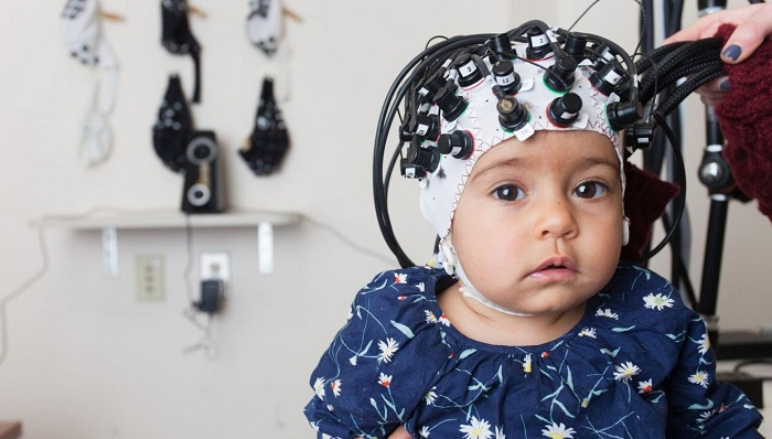 An infant in the Functional Near-Infrared Spectroscopy neuroimaging lab. (Kathleen Krol)
